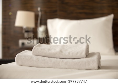 Stacked clean white bath towels on the bed sheets in hotel room, close-up - stock photo