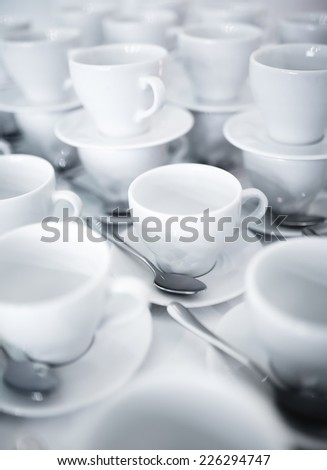 Stacked coffee and tea cups on saucers with silver teaspoons - stock photo