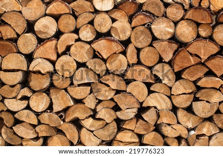 Stacked logs of spruce with whole, half and quartered logs with bark  - stock photo