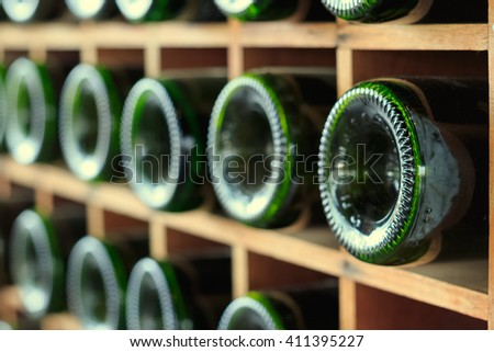 stacked of old wine bottles in the cellar - stock photo