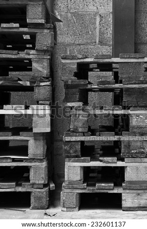 Stacked pallets in old factory in black and white - stock photo