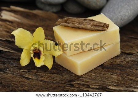 Stacked soap and yellow orchid with stones on Driftwood - stock photo