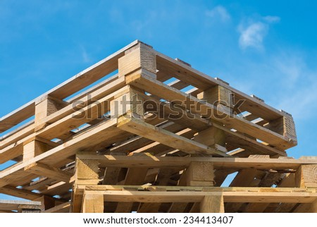 stacked up pallets against a blue sky - stock photo