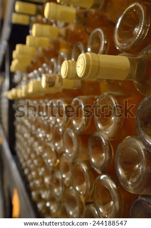 stacked up wine bottles in the cellar, dusty but tasty - stock photo