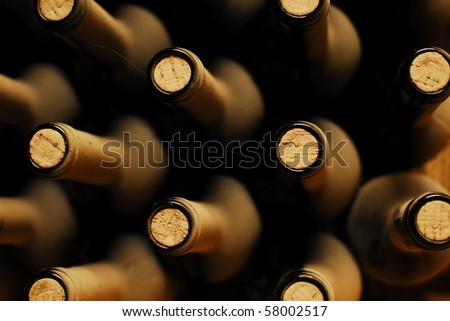 stacked up wine bottles in the cellar, dusty but tasty. - stock photo