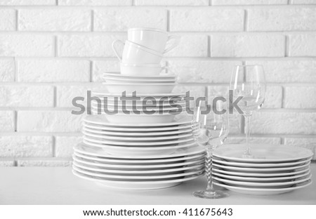 Stacked white clean plates, glasses and cups on  white table - stock photo