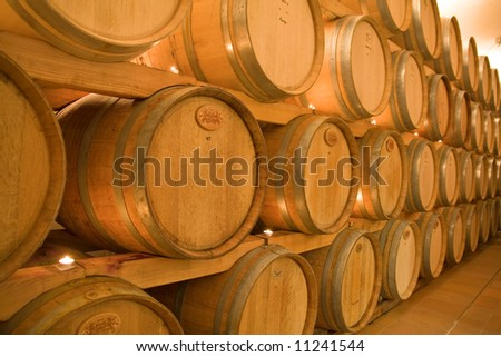 stacked win barrels in the wine cellar - stock photo
