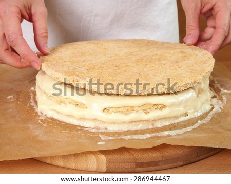 Stacking layers. Making Chocolate Layer Cake with Cream Cheese Filling and Chocolate Topping. Series. - stock photo
