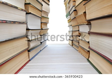 Stacks of books making a corridor with white copyspace in the end - stock photo