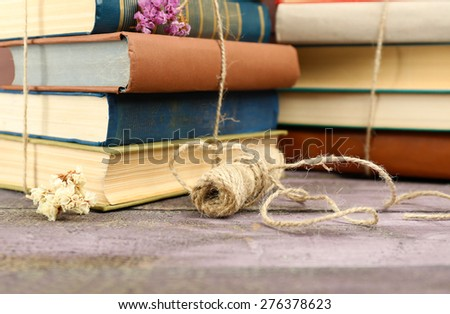 Stacks of books with dry flowers and twine on table close up - stock photo