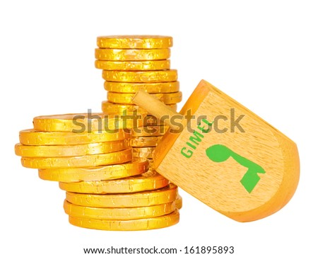 Stacks of Chanukah coins, gelt, large wooden dreidel. Traditional game for the Jewish holiday of Chanukah. The Hebrew letter gimel wins the group of shiny yellow coins. Isolated on a white background. - stock photo