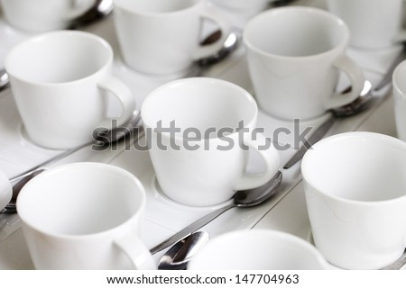 Stacks of coffee cups on saucers with silver teaspoons - stock photo