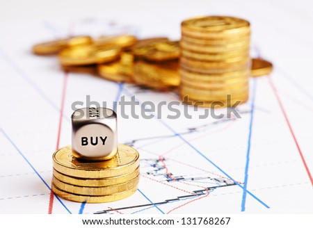 Stacks of coins, dices cube with word BUY  and a up trend chart as the background. Successful trading. Selective focus - stock photo