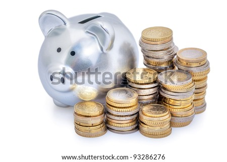 Stacks of Euro coins next to a silver piggy bank.  White background - stock photo