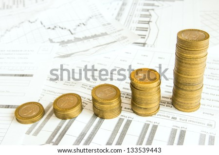 Stacks of gold coins like increasing columns over different paper documents background. Earnings or saving graph (diagram). - stock photo