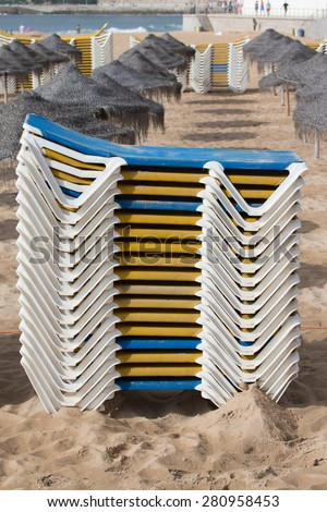 Stacks of loungers and thatched umbrellas on a sandy beach of Estoril. Portugal. - stock photo