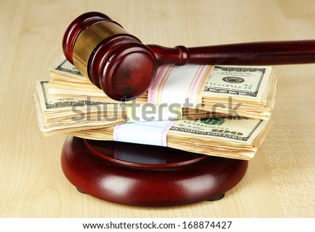 Stacks of money and judges gavel on wooden table - stock photo