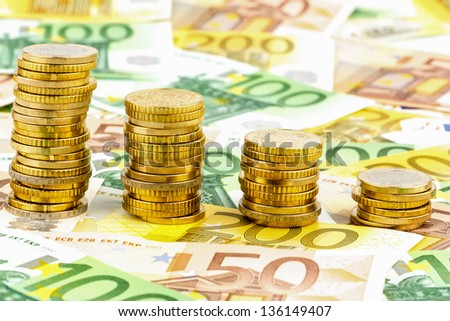 stacks of money coins, falling curve, symbol photo of falling interest rates and falling costs - stock photo