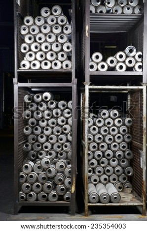 Stacks of new silencers mufflers car before distribution and retail. Detail of a new automotive components in stainless steel inside a industrial warehouse. - stock photo
