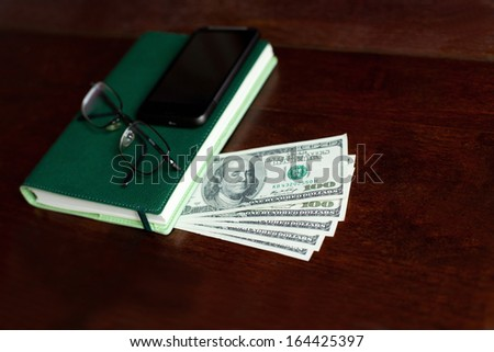 Stacks of one hundred dollars banknotes, notebook, pen and glasses on wooden desk - stock photo