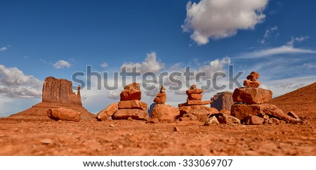 Stacks of prayer rocks or cairns lined up in Monument Valley desert - stock photo