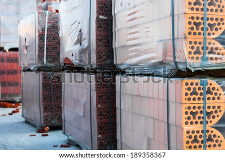 Stacks of silicate bricks on wooden pallets and in polyethylene  - stock photo