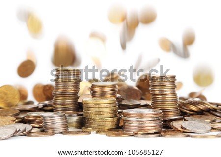 stacks of silver and golden coins and falling coins on background isolated - stock photo