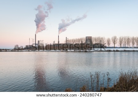 Stacks of smoke from the chimneys of the power plant with a high concrete cooling tower. - stock photo