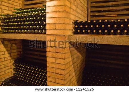 stacks of wine bottles lying on the shelves - stock photo