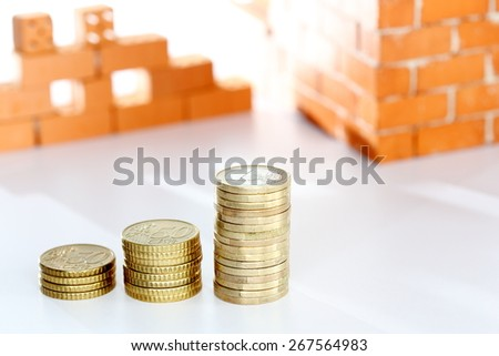 stacks with coins and brick wall in background - stock photo