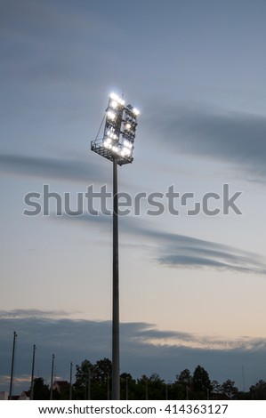 Stadium lights on a sports field at evening with dilapidated - stock photo