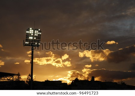 Stadium lights turned on and a beautiful sunset in the background - stock photo