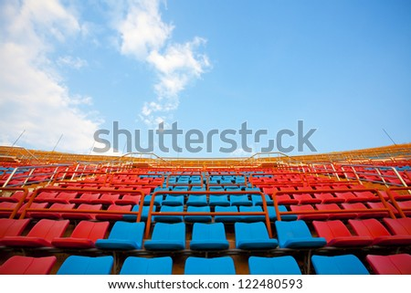 stadium seats, red  and blue seats on stadium steps bleacher up bright sky - stock photo