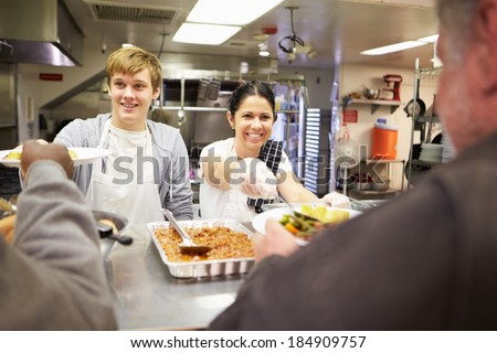 Staff Serving Food In Homeless Shelter Kitchen - stock photo