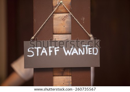 Staff wanted inscription on a board hanging on wooden post. - stock photo