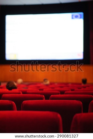 Stage with podium and big screen. People at conference hall, rear view. Soft focus - stock photo
