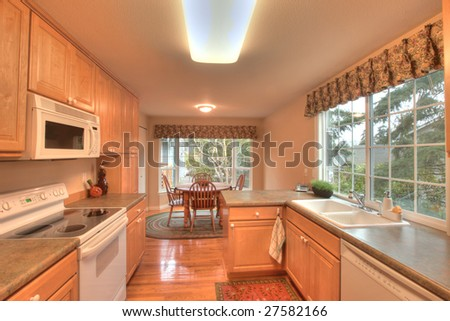 Staged kitchen with dining room in townhouse - stock photo