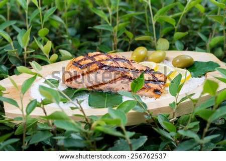 stages of cooking salmon on the grill - cook a delicious salmon fillet grilled served on a wooden plate with olives and lemon sea salt - stock photo