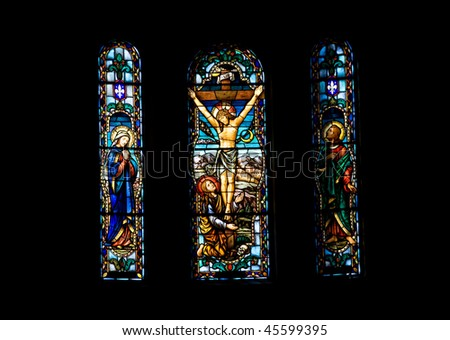 Stained glass church window depicting Jesus on the cross - stock photo