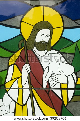 Stained glass image of Jesus with a lamb.  Like a sheppard taking care of his flock. - stock photo