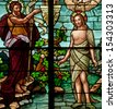 Stained glass window depicting Bible story of Saint John the Baptist baptizing Jesus in the Jordan River - stock photo