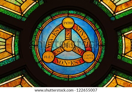 Stained glass window depicting doctrine of the Holy Trinity in Latin with symbols of circle and triangle - stock photo