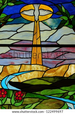 Stained glass window depicting Holy Spirit in form of a dove hovering over creation - stock photo
