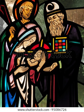 Stained glass window depicting the Presentation of the infant Christ in the temple, with Mary, Joseph and Simeon - stock photo