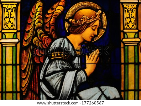 Stained glass window of angel with hands folded in prayer - stock photo