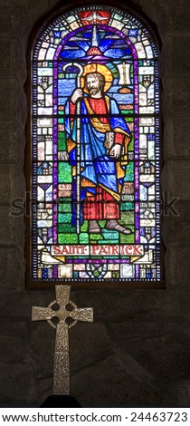 stained glass window of saint patrick with celtic cross in foreground - stock photo