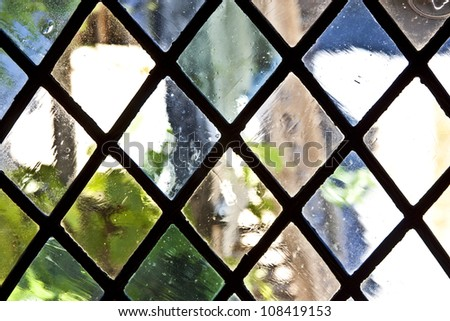 stained glass with metal diamond shaped frames - stock photo