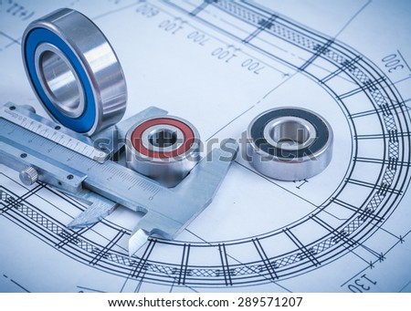 Stainless rolling bearings and slide caliper on blueprint construction concept. - stock photo