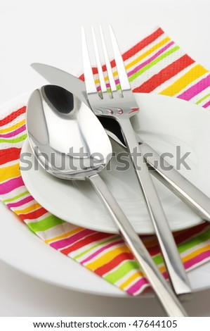 Stainless spoon, fork and knife on white plates with multicolored striped paper napkin. - stock photo