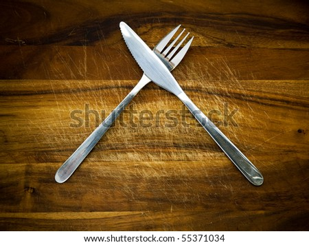 Stainless steel cutlery on a wooden chopping board - stock photo